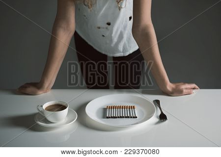 Harmful Breakfast. Woman Standing At The Desk With Coffee And Plate Full Of Cigarettes