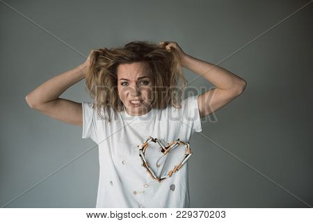Waist Up Portrait Of Miserable Girl With Cigarette Heart On T Shirt Pulling Her Hair. Isolated On Ba