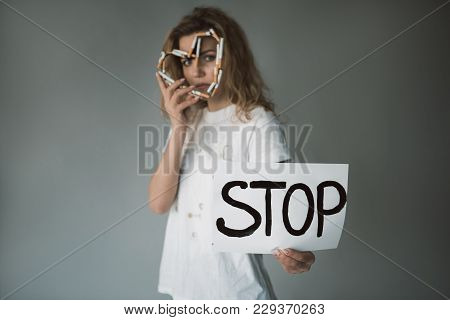 Waist Up Of Serious Woman Covering Face With Heart Made Of Tobacco And Showing Stop Word On Paper. F