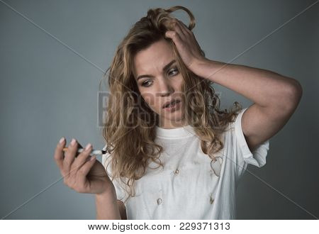 Portrait Of Upset Woman With Ciggy In Hand Having Headache From Tobacco Fume. Isolated On Background