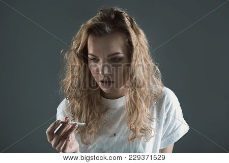 Unhealthy Lifestyle Concept. Portrait Of Miserable Woman Standing And Holding Burning Cigarette. Iso