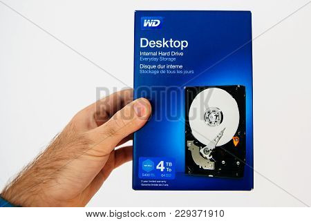 Paris, France - Feb 21, 2018: Man Holding Against White Background Blue Box With New Hdd Hard Disk D