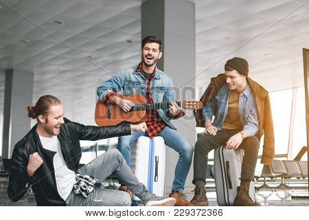 Cheerful Man Performing Melody With Musical Instrument While Sitting Near Friends In Airport. Inspir