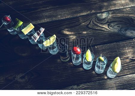 A Number Shots Of Alcohol. Shots With Alcohol Top View On The Wooden Surface. Over Every Shot Someth
