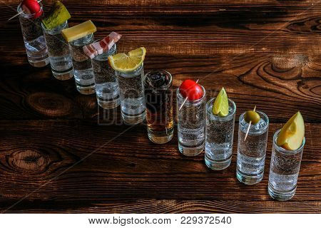 Shots With Alcohol On Wooden Background. Ten Shots Of Alcohol On A Wooden Table. On Each Shot, On To