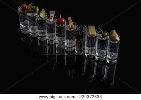 Shots Of Alcohol On The Black Glass. Inside The Ice Cubes. On Each Shot, On Top Of That Lies - Radis