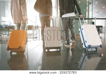 Three Male Friends Keeping Luggages While Going In Airport. Trip Concept
