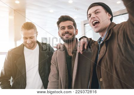 Portrait Of Cheerful Young Comrades Standing Indoor. Conversation And Fellowship Concept