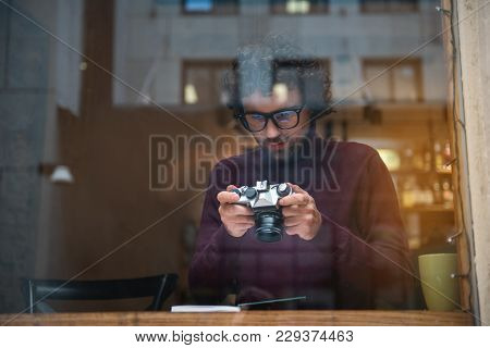 Cheerful Male Photographer Is Watching Shots On Camera Screen With Interest. He Is Sitting At Table