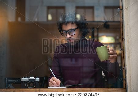 Portrait Of Pensive Young Man Writing Poem With Inspiration. She Is Drinking Coffee While Sitting At