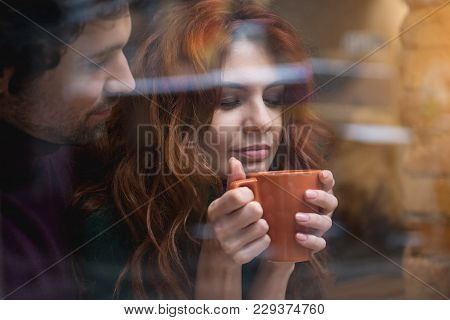 Portrait Of Relaxed Red-haired Girl Smelling Coffee Aroma With Closed Eyes. Man Is Looking At Her Wi