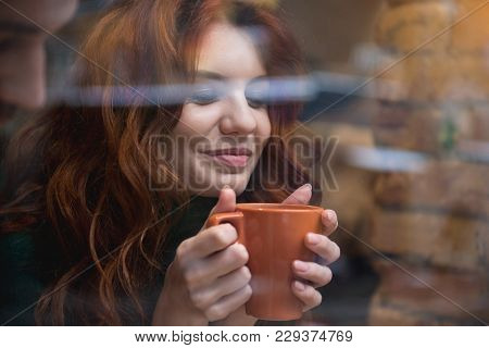 Portrait Of Happy Young Woman Enjoying Hot Beverage Near Window. She Is Holding Cup And Closed Eyes