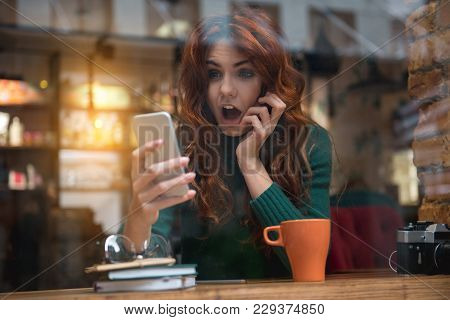 Shocked News. Portrait Of Terrified Girl Looking At Her Mobile Phone And Screaming. She Is Sitting A