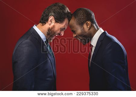 Side View Profile Of Angry Young Colleagues Are Fighting Each Other With Foreheads Together, Staring