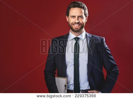 Success Sharing. Waist-up Portrait Of Cheerful Young Elegant Bearded Businessman Is Standing With Fo