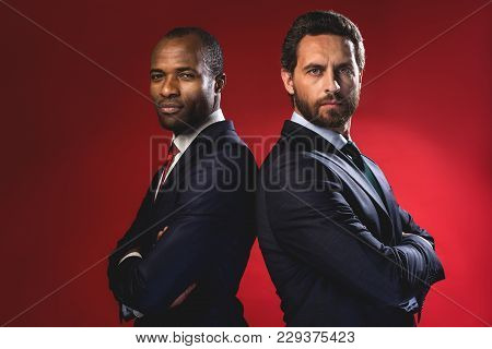 Confident Business. Waist-up Portrait Of Young Serious Businessmen Are Standing With Crossed Arms Ba