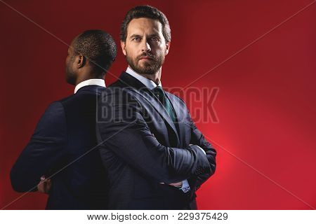 Professional Team. Portrait Of Serious Young Bearded Manager Is Standing With Crossed Arms While Loo