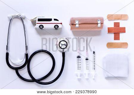 Syringe, Stethoscope, Medical Elastic Bandage, Adhesive Bandages And Medical Gauze Bandage On A Whit