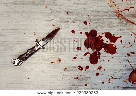 Conceptual Image Of A Sharp Knife With Blood On It Resting On A Concrete Floor. Concept Photo Of Mur