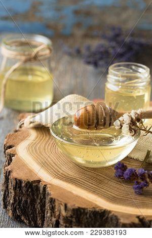 Honey. Honey And Honey Dipper On Rustic Oak Table. Hot Herb Tea In The Background.
