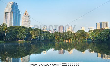 Modern Bangkok Building City With Reflection Of Water And Urban Garden Park Green Space Landscape An