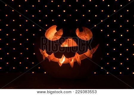 Funny Orange Pumpkin Like A Head With Carved Eyes And A Smile On A Black Background With A Garland F