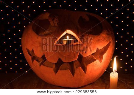 Orange Pumpkin As A Head With Carved Eyes And A Smile With Burning Candles On A Black Background Wit