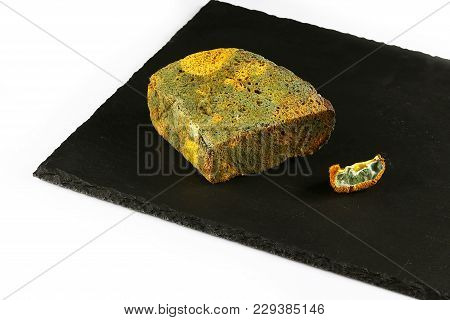 Half A Loaf Of Mouldy Rye Bread And A Piece Of Kiwi With A Mold On A Black Shale Board Isolated On W
