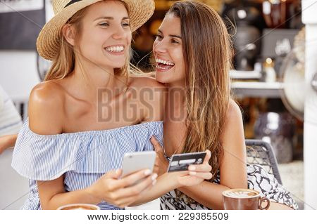 Happy Female Lesbians Have Date At Cafe, Drink Hot Tasty Cappuccino And Make Purchases Online, Use M