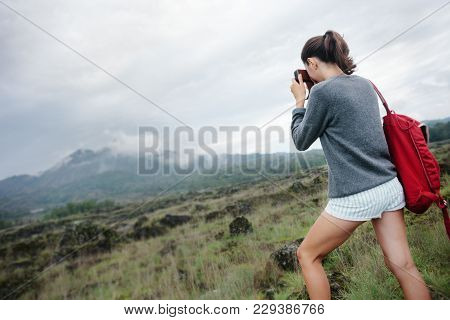 Young Traveling Girl Taking Photo Of Volcano In The Wild