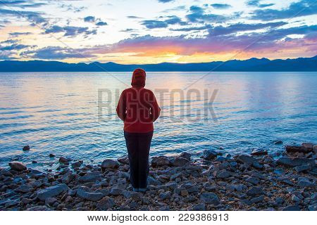 A Woman On The Shore Of A Big Lake Admires The Sunset