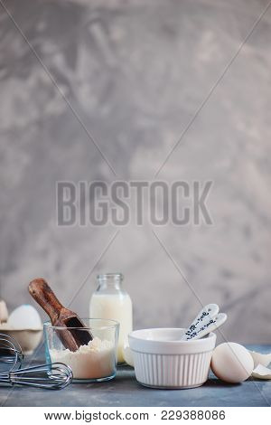 Baking Tools And Ingredients Concept In High Key. Baking Forms, Whisk, Flour Scoop, Eggs And A Bottl