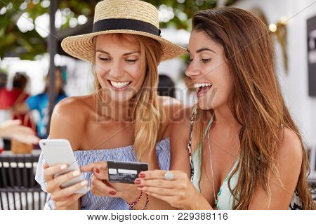 Cheerful Best Friends Women Meet Together At Cafeteria, Happy To Make Online Shopping With Smart Pho