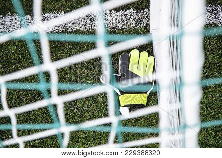Top View Of Goalkeeper Gloves Lying On Soccer Pitch