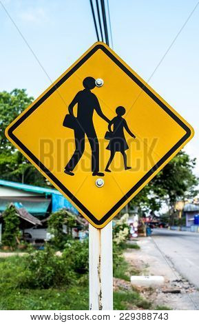 School Zone Sign Post With Sky, Road, Tree, And House At Countryside