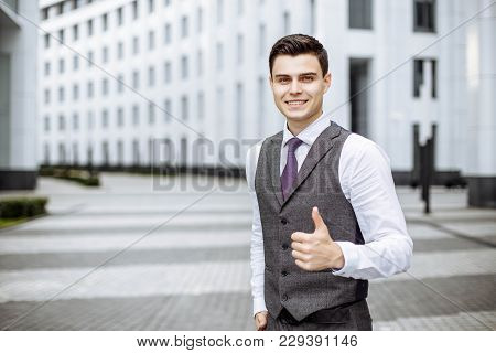 Life Is Great. Positive Upbeat Handsome Businessman Shows Thumb Up And Smiling While Standing In Fro