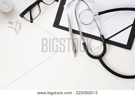 Doctors Office Desk With Thermometer And Medical Instruments On White