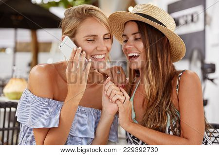 Lovely Lesbian Couple Have Fun, Laugh Joyfully And Keep Hands Together, Have Mobile Conversation, Si