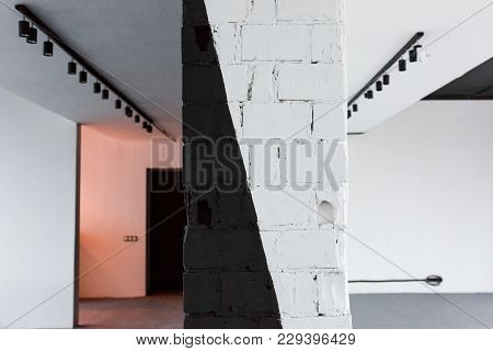 Empty Office Room With Brick Painted In Black And White Wall In Front Focus. Loft Interior Design Wi