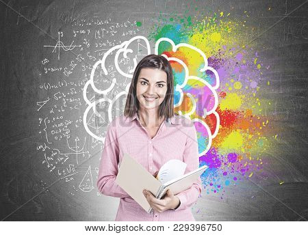 Portrait Of A Smiling Young Woman Wearing A Pink Shirt And Holding An Open Copybook. A Blackboard Ba