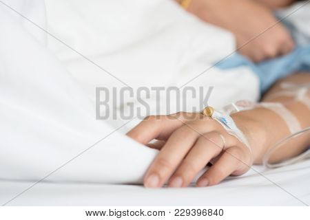Selective Focus On Woman Patient's Hand Receiving Saline Solution By Intravenous Injection Be Treate
