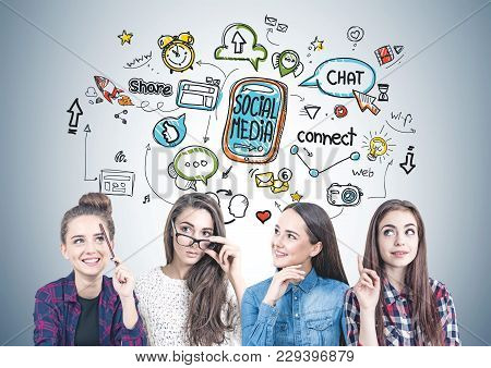 Four Teen Girls In Casual And Formal Clothes Are Standing Together And Brainstorming. A Gray Wall Ba