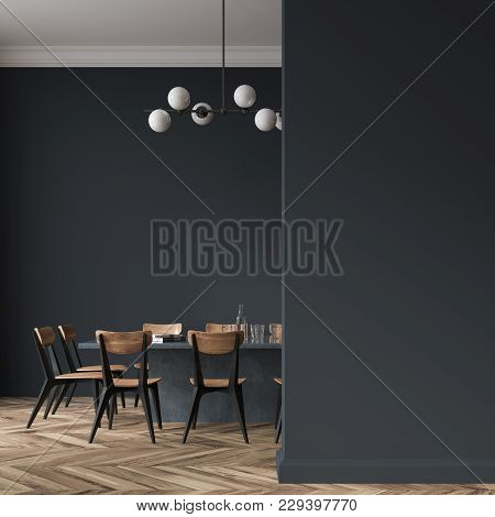 Long Black Dining Room Table With Black And Wooden Chairs Standing In A Black Room. A Blank Wall Fra