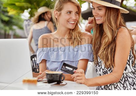Outdoor Portrait Of Stylish Female Lesbians Browses Internet On Modern Portable Laptop Computer, Mak