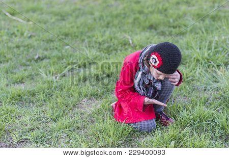 Child Girl Seeking Something On Grass Lawn By Spring