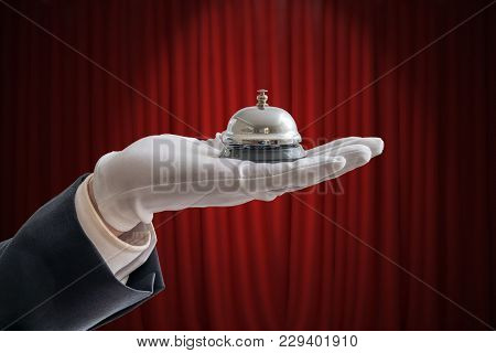 Hand In White Glove Is Holding Service Bell. Red Curtain In Background.