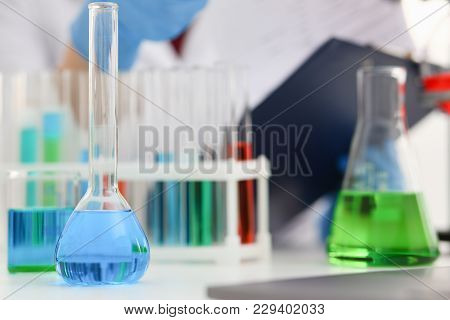 Chemical Industry Bulb With Blue Magenta Pink Liquid Lab Tubes Stand On The Table In The Laboratory