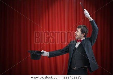 Happy Magician Or Illusionist Is Showing Magic Trick. Red Curtains In Background.