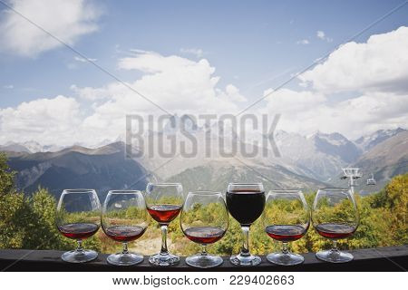 Six Glasses Of Cognac And One Glass Of Red Wine Stand Against The Backdrop Of A Beautiful Mountain L