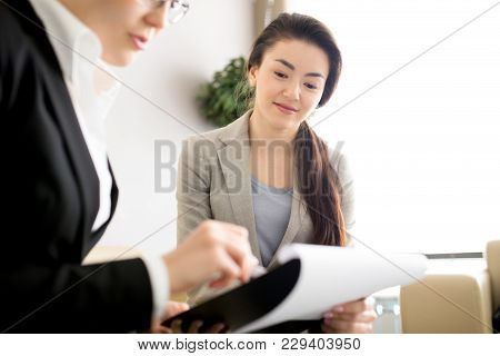 Pretty Young White Collar Worker Listening To Her Female Colleague With Interest While She Presentin
